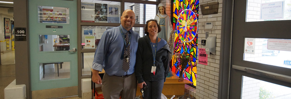 Two parent volunteers in front of the Mary statue and a multi-coloured stained glass window