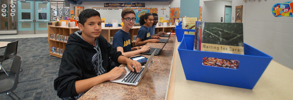 Four students in a row working on laptops at a table